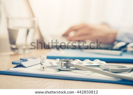 Healthcare and medical concept. Medicine doctor's working place. Focus on stethoscope, doctor's hands typing something on background. Copyspace - stock photo