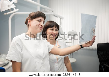 healthcare and medical concept - two doctors dentists looking at x-ray