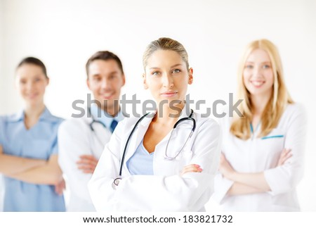 healthcare and medicine concept - attractive female doctor in front of medical group in hospital - stock photo