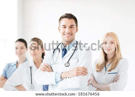 healthcare and medicine concept - attractive male doctor in front of medical group - stock photo