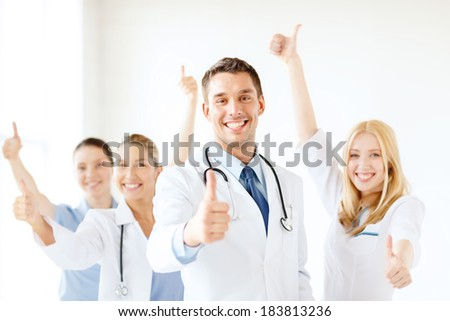 healthcare and medicine concept - attractive male doctor in front of medical group in hospital showing thumbs up - stock photo