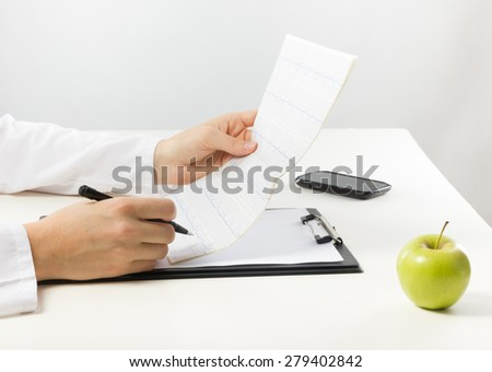 Healthcare and medicine concept - doctor with medical clipboard and green apple analyzing cardiogram results - stock photo