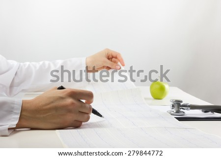 Healthcare and medicine concept - doctor with medical stethoscope and green apple analyzing cardiogram results - stock photo