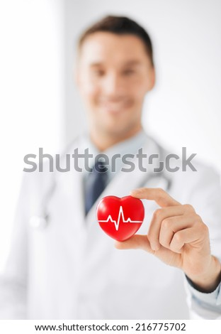 healthcare and medicine concept - male doctor holding red heart with ecg line - stock photo