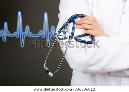 Healthcare and medicine concept. Male doctor with stethoscope and cardiogram