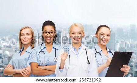 healthcare and medicine concept - smiling female doctor and nurses with stethoscope - stock photo