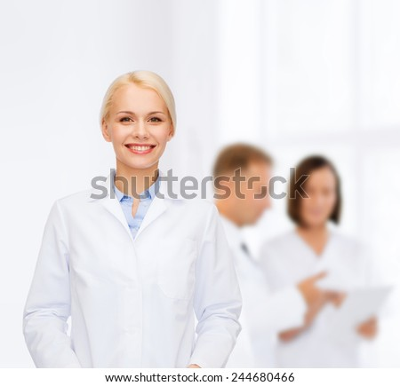 healthcare and medicine concept - smiling female doctor over group of medics in hospital - stock photo