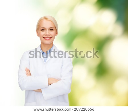 healthcare and medicine concept - smiling female doctor over natural background - stock photo