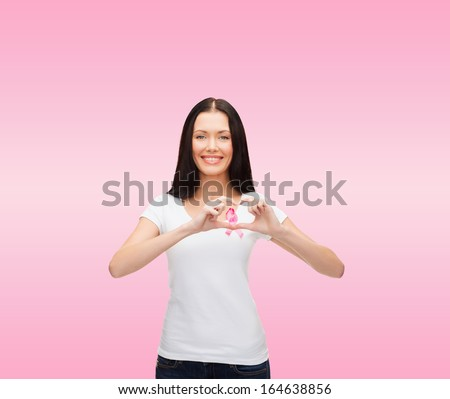 healthcare and medicine concept - smiling woman in blank white t-shirt with pink breast cancer awareness ribbon showing heart shape - stock photo