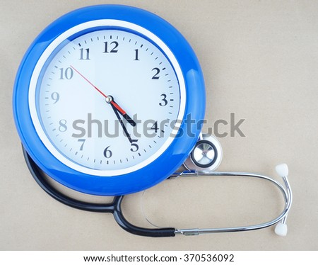 healthcare and medicine concept -  wall clock and stethoscope - stock photo