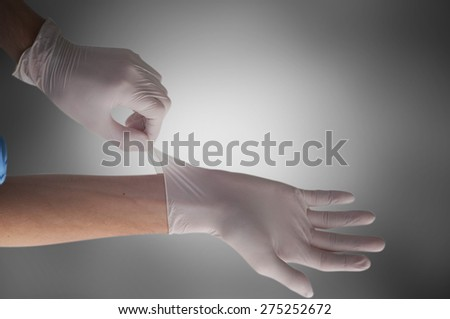 Healthcare And Medicine. Doctor putting on protective gloves - stock photo