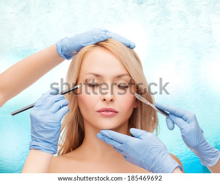 healthcare, beauty and medicine concept - beautiful woman face with closed eyes and beautician hands with pencil and scalpel - stock photo