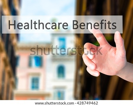 Healthcare Benefits - Hand pressing a button on blurred background concept . Business, technology, internet concept. Stock Photo - stock photo
