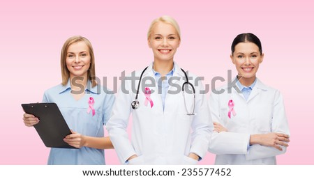 healthcare, charity, support and medicine concept - group of female doctors with pink breast cancer awareness ribbon - stock photo