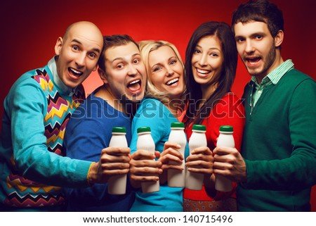 Healthcare concept: Portrait of five stylish close friends hugging, smiling, holding plastic bottles with milk (yoghurt) and posing over red background. Healthy white teeth. Hipster style. Studio shot - stock photo