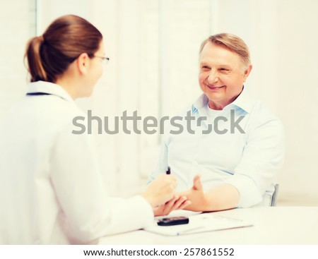 healthcare, elderly and medical concept - female doctor or nurse with patient measuring blood sugar value - stock photo