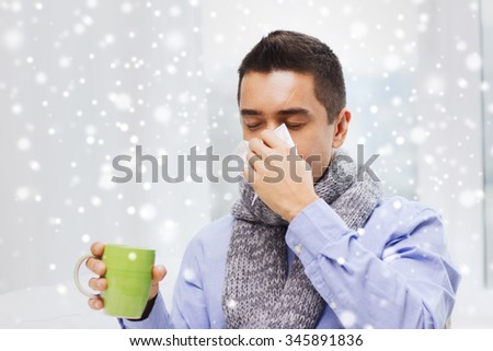 healthcare, flu, people, rhinitis and medicine concept - ill man blowing his nose with paper napkin and drinking tea at home over snow effect - stock photo