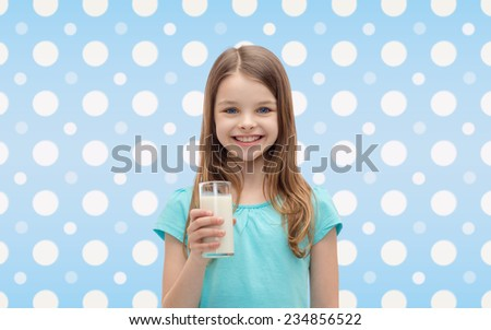 healthcare, food, drinks, childhood and people concept - smiling little girl with glass of milk over blue white polka dots pattern background - stock photo