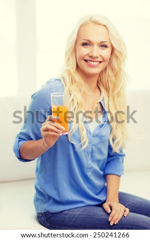 healthcare, food, home and happiness concept - smiling young woman with glass of juice having breakfast at home