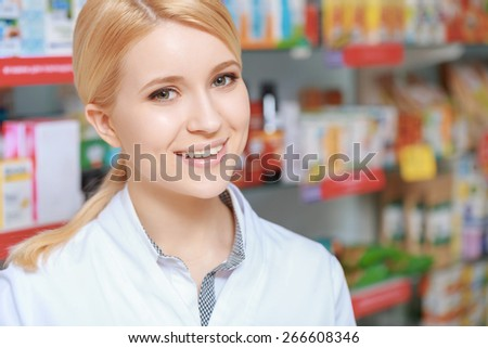 Healthcare in action. Close-up of an attractive young pharmacy chemist and blurred rows of medicine on the background - stock photo