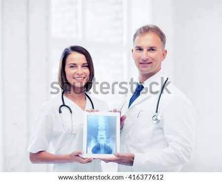 healthcare, medical and radiology concept - two doctors showing x-ray on tablet pc - stock photo