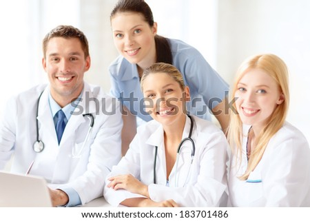 healthcare, medical and technology concept - smiling group of doctors with laptop computer in hospital - stock photo