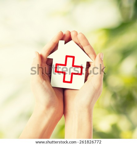 healthcare, medicine and charity concept - hands holding white paper house - stock photo