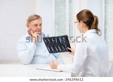 healthcare, medicine and elderly concept - female doctor with old man looking at x-ray - stock photo