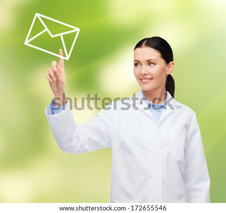 healthcare, medicine and technology concept - smiling female doctor pointing to envelope - stock photo