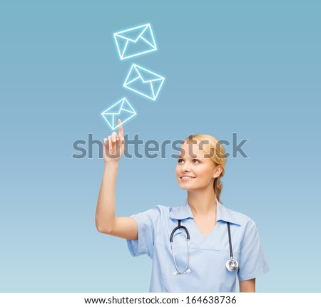 healthcare, medicine and technology concept - smiling young doctor or nurse pointing to envelope - stock photo