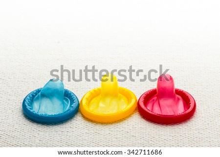Healthcare medicine, contraception and birth control. Closeup colorful condoms on white cloth. - stock photo