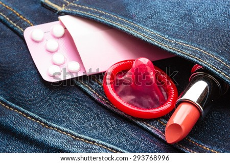 Healthcare medicine, contraception and birth control. Closeup oral contraceptive pills, condom and red lipstick in denim pocket. - stock photo