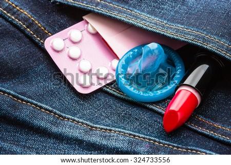 Healthcare medicine, contraception and birth control. Closeup oral contraceptive pills, condom and red lipstick in denim pocket. - stock photo