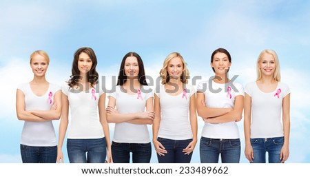 healthcare, people and medicine concept - group of smiling women in blank t-shirts with pink breast cancer awareness ribbons blue sky background
