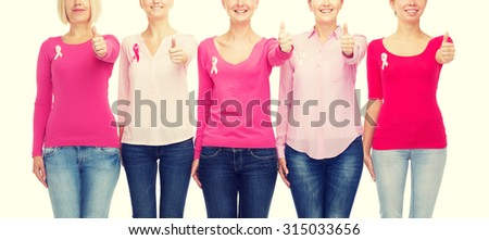 healthcare, people, gesture and medicine concept - close up of smiling women in blank shirts with pink breast cancer awareness ribbons over white background - stock photo