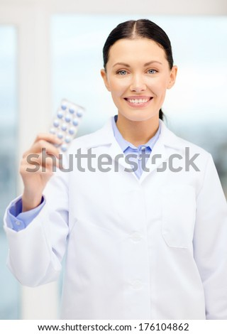 healthcare, pharmacy and medicine concept - smiling young doctor with pills in cabinet - stock photo