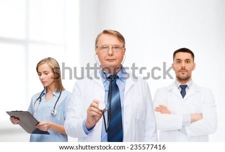 healthcare, profession and medicine concept - group of doctors in white coats with clipboard and stethoscope over clinic background - stock photo