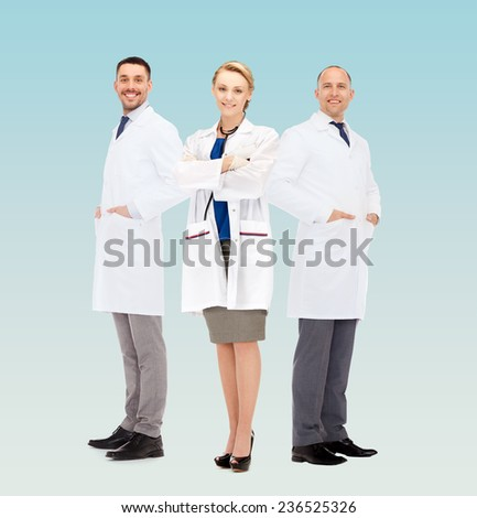 healthcare, profession and medicine concept - group of smiling doctors in white coats over blue background - stock photo