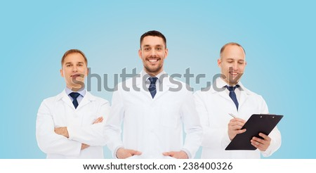 healthcare, profession and medicine concept - group of smiling male doctors in white coats with clipboard and stethoscope over blue background - stock photo