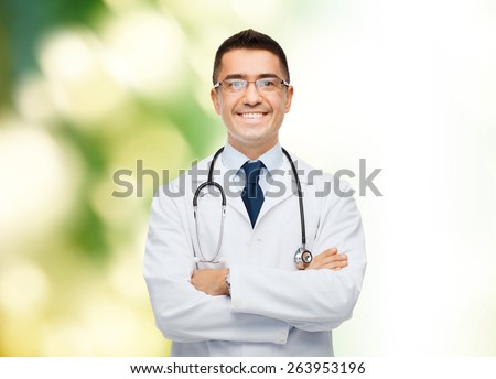 healthcare, profession, people and medicine concept - smiling male doctor in white coat over green background - stock photo