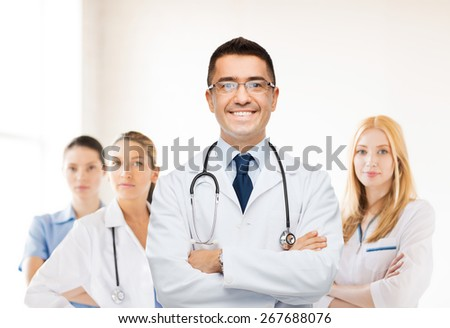 healthcare, profession, people and medicine concept - smiling male doctor in white coat over group of medics at hospital background - stock photo
