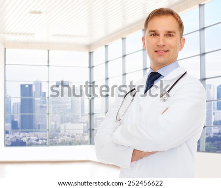 healthcare, profession, people and medicine concept - smiling male doctor with stethoscope in white coat over clinic background - stock photo