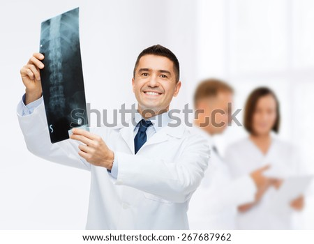 healthcare, rontgen, people and medicine concept - smiling male doctor in white coat with x-ray over group of medics at hospital background - stock photo