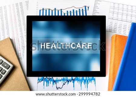 healthcare word on tablet with financial graph background - stock photo