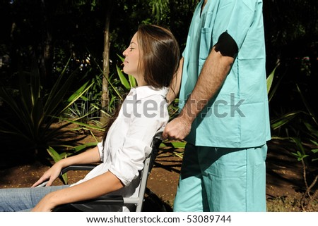 healthcare worker pushing a young woman in a wheelchair - stock photo