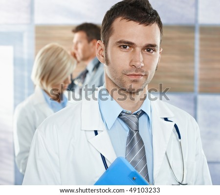 Healthcare workers on hospital corridor mid-adult doctor in front looking at camera, smiling. - stock photo