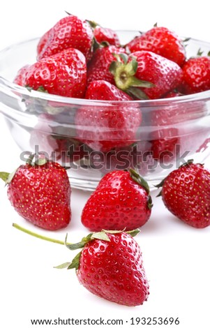 healthily raised organic strawberries in a glass bowl on white