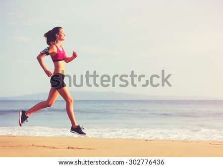Healthy Active Lifestyle. Young sports fitness woman running on the beach at sunset. - stock photo