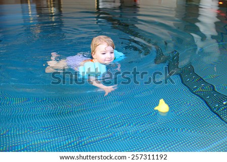 Healthy active little child, laughing blonde toddler girl swimming in the pool learning to float using armbands  - stock photo