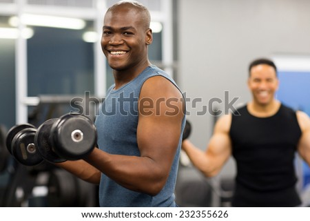 healthy african man working out with dumbbells in gym - stock photo